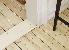 Etter å ha revet av gamle vegg-til-vegg-tepper, fant man frem til det originale tregulvet. Det ble slipt ned og behandlet med UV-filter og lakket med vannbasert gulvmaling, tre strøk .  Det passer godt til de lyse veggene. Listverket med fotkloss er gedigent og stilriktig.