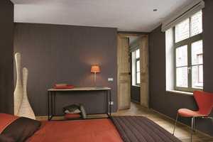 Et dramatisk og varmt soverom har det blitt med dypbrunt tapet på veggene. Mønsteret, bregneblader er typisk for tiden. (Kosy/Storeys)