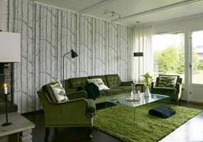 Fondveggen i kjellerstuen er tapetsert i et mønster av grå trestammer (Cole & Son, fra Interiøragenturer). Det gamle sofamøblementet fikk fornyet glans sammen med nytt glassbord og gulvteppe i ull og lin.