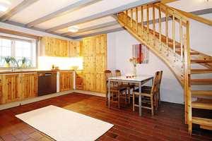 Før: Kjøkkenet hadde mørke terrakottafliser på gulvet og furuinnredning med mye kvist. Den lakkerte furutrappen virket veldig dominerende.