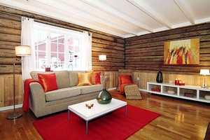 Før: Stuen hadde tunge farger, med tre ulike tresorter i det lille rommet. Tømmeret var supplert med brystpanel i furu, og på gulvet var det blanklakkert parkett.