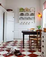 <b>GULV:</b> Det røde og hvite sjakkrutete gulvet er et skikkelig blikkfang. Det har fått litt støtte i den stripete gardinen og de mønstrede tallerkenene på veggen. Farge på gulv er Lust og Mjölk fra Beckers.