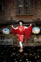 Østens mystikk: Kjole i rød tapet, ermer i trågardiner, belte i rød vinyl med pålimt rødt teppe. Armbåndet er av røde mosaikkfliser. Modellen bærer en gardinstang med to dekorerte rislamper.