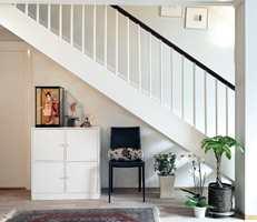 Skapet ble malt hvitt, og sammen med stolen og de grønne plantene skaper det en hyggelig plass under trappen.