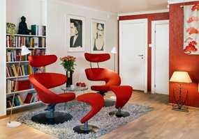 En dør ble fjernet, og med en hel vegg ble det enklere å plassere både bøker og møbler. Stolene er stilige dekorelementer, og skaper fargebalanse mot den røde veggen.