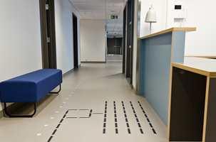 <b>TAKTIL MERKING:</b> I gulvet er det felt inn både taktile ledelinjer og markeringer av rømningsveier som blir selvlysende i mørket. Kapsel Design har utformet arbeidsskranker og faste stasjoner i bygget.