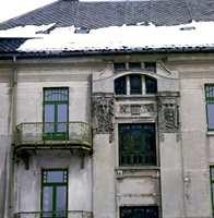 Typisk murgård i jugendstil med masker på fasaden og buede vinduer.