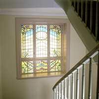 Vinduene i murgården sett innenfra. Farget glass med vakre plantemotiver gjorde det til en opplevelse å ferdes i oppgangen.