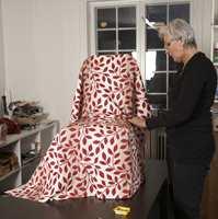 Etter at tekstilet er klippet, foldet hun den fremste delen inn langs stolsetet.