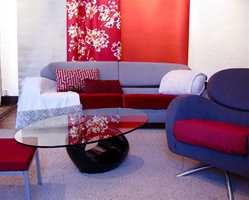 Vakre, røde gardiner, puter og tepper kan gi julestemning uten at de er typisk julestoffer. Kombinert med lilla stol blir det riktig flott. Alle stoffene er fra Intag.
