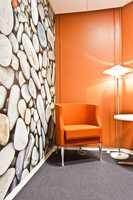 I et lite samtalerom eller telefonrom har den ene veggen et fototapet med småsteiner. Én rødfarget stein matcher med den oransje veggfargen.