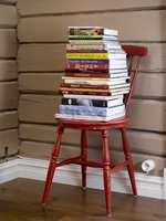 Den gamle stolen har fått nytt bruksområde og fungerer utmerket som en annerledes og fargerik bokhylle for kokebøkene.