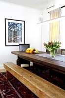 Spisebordet har eieren tegnet selv, og materialene er vindfall fra farsgården. Sittebenken er arvet etter oldefar. Spisestolene i mørkbrunt skinn er valgt for å gi sittekomfort i mange timer.