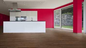 Rommet på bildet er et av galleri-bildene som finnes å velge blant i designstudioet til Kronotex. Her har vi valgt Smartpanel Trend Real Red, montert liggende på veggene, og Kronotex Exquisit 3070 Valnøtt Toscanca, lagt parallelt med lysinnfallet fra vinduene.