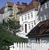 Husrekke i Bergen med mange varianter over tidens stil. Panel utformet som halvsøyler dekker tømmerhjørnene. Det hvite huset har også søyler ved inngangen og typisk tannsnittbord ved gesimsen.