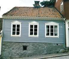 Også små hus fikk moteklær mot gaten, som dette huset i Halden. Grå steinfarge, tempelgavler over vinduene og tannsnittbord gjorde det veldig moderne da det ble bygget omkring 1826. Huset har også typiske empirevinduer.