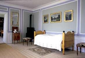 Finere interiører fikk ofte veggene delt opp i felter ved hjelp av listverk. Feltene kunne males i ulike farger eller tapetseres. Dette er et soverom fra Rød herregård i Halden.