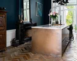 <b>KLASSISK TRENDY:</b> På kjøkkenet møter marmor og klassisk fiskebeinsgulv moderne innredning og elementer, og alt spiller på lag og fremhever hverandre. Veggene er malt med Licetto i fargen Steel Blue.