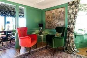KORALL: Den friske korallfargen fra tapetet i gangen dukker opp som en livlig kontrast i den grønne stuen.