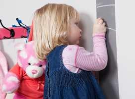 <b>LA HØYDEN BESTEMME</b> Knaggene er montert innen barnets rekkevidde. Det gråmalte feltet på veggen er til merking av hvor mye hun har vokst det siste året, og sparer dørkarmen for tusjmerker. (Foto: Kristian Owren/ifi.no)