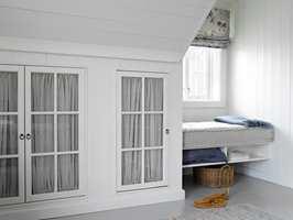 Skapdører med glass og gardin gir ekstra romfølelse, bryter opp og skaper litt ekstra dybde i veggen.