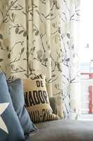 Grenmønsteret fra tapetet blir tatt opp igjen med et annet grenmønster på gardinene.