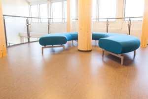 <b>SOFA:</b> Som et lite statement fra vår tid snor det seg en rund sofa rundt en søyle av tre mot trappeløpet. På gulvet er det lagt en homogen vinyl som matcher gulvet i det «gamle» bygget.