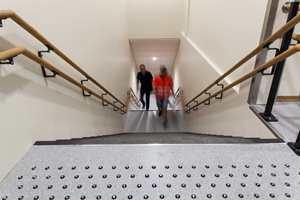 <b>TAKTILT:</b> I tråd med kravene til universell utforming er det doble håndløpere, og taktil merking med «knotter» i farefeltet på toppen av trappen, samt striper i oppmerksomhetsfeltet ved inngangen til trappen.