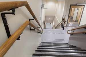 <b>HELHET:</b> En trappegang med belegg i trappa. Veggene er sandsparklet og malt. Den lyse veggfargen og det gråmelerte vinylbelegget er gjennomgående i bygget.