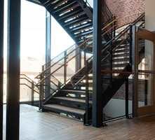 <b>GAMMELT OG NYTT:</b> Ytterveggen fra det gamle bygget bringer noe av den gamle atmosfæren inn i nybygget. Massivt parkettgulv, den sorte trappen og sortmalte søyler tar det videre inn i vår tid.
