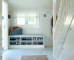 En praktisk skohylle med sittebenk  er bygget på stedet, og holder orden i familiens skotøy. Liftgardinens tynne tekstil slipper lyset delvis igjennom.