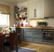Den gamle kjøkkeninnredingen fikk nye dører med moderne beslag av børstet stål. Krydderhylla ble skjult bak en skapdør belagt med rustfritt stål.