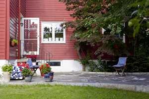 <b>BLÅ DETALJER:</b> Blåfargene er nydelige mot den røde husfargen. De gjentas i puter og krukker, som bidrar til å binde sammen uteplassen.