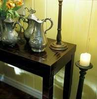 En samling kopier av gamle 1700-tallsmodeller i tinn gir en touch av fransk herregård, her arrangert som et stilleben på et konsollbord i skinn.