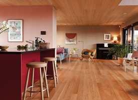 <b>LIVSROM: </b>Huset er i tre etasjer, med kjøkken og stue i første etasje. Kjøkken, spisestue og stue i en stor og åpen løsning med massive eikegulv og tak i økosertifiserte eikefinerte plater. Gulv og tak er av hardvoksoljet eik. Den morsomme lenestolen fra Finn Juhl er et lekent innslag i stuen og en hyllest til Emelies far som var møbeltapetserer.
