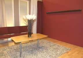 Fondvegg i et sterkt rødt innslag, mens de andre veggene er malt i beige. Parketten er i lønn og teppet en flossvariant.