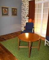 Den blå malte veggen kombinert med en blomstret tapet. Den mørke parkett matcher både møbel og gardin.