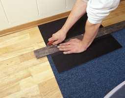 Skjær i flisen fra baksiden. Skjær der som den siste monterte flisen slutter. Bruk rett knivblad, og hold kniven loddrett ned i teppeflisen. Bruk stållinjal som støtte.