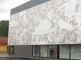 Fasaden er kledd med antrasittfarget teglstein i kombinasjon med perforerte aluminumsplater. Fasadeplatene er trukket foran enkelte vindusflater.