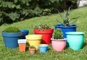 OMMERBLOMSTER: Mal de gamle krukkene dine i friske farger, og fyll dem med blomster. Sett dem i grupper der du trenger en fargeklatt.