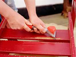 Gammel løstsittende maling skrapes vekk før et nytt strøk påføres. Foto: Nordsjö