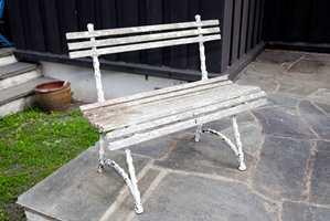 Den hvitmalte benken bar preg av mye vær og mange år.