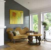 Runde former på sofa og bord står i sterk kontrast til det moderne maleriet og vinklene i rommet.
