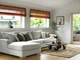 Det blankmalte, lysegrå panelet står i spennende kontrast til de varme jordfargene som sees både ute og inne.