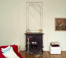 Et marmoret felt med enkel strekdekor i nisjen på veggen framhevet den vakre støpejernsovnen.