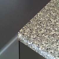 Benkeplatene i laminat er mykt buet i fronten. I våtsonen er det valgt et terrazzomønster i gråtoner. For øvrig er benkene grå som frontene.