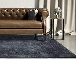 <b>MIDTSTILT:</b> Et løst teppe bør ligge midtstilt i forhold til sofaen, det skal være noe bredere enn sofaen og ligge litt under den. (Foto: Teppeabo)
