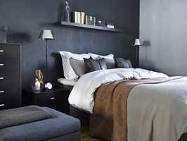 Den mørke veggen på soverommet er kledd med et tapet med dyremønster.