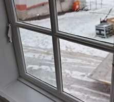 <b>1814:</b> Når man titter ut gjennom vinduene på Eidsvoldsbygningen, glir blikket forbi vindussprosser i en svak grånyanse. (Foto: Kristian Owren/ifi.no)