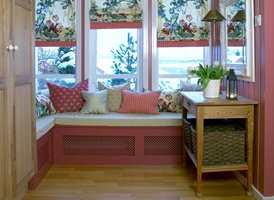 <b>AVSTEMT</b> Vindusveggen ble til en hyggelig krok. Benkene, i samme farge som veggen, skjuler panelovner, og rottingen slipper varmen ut. (Foto: Mona Gundersen)